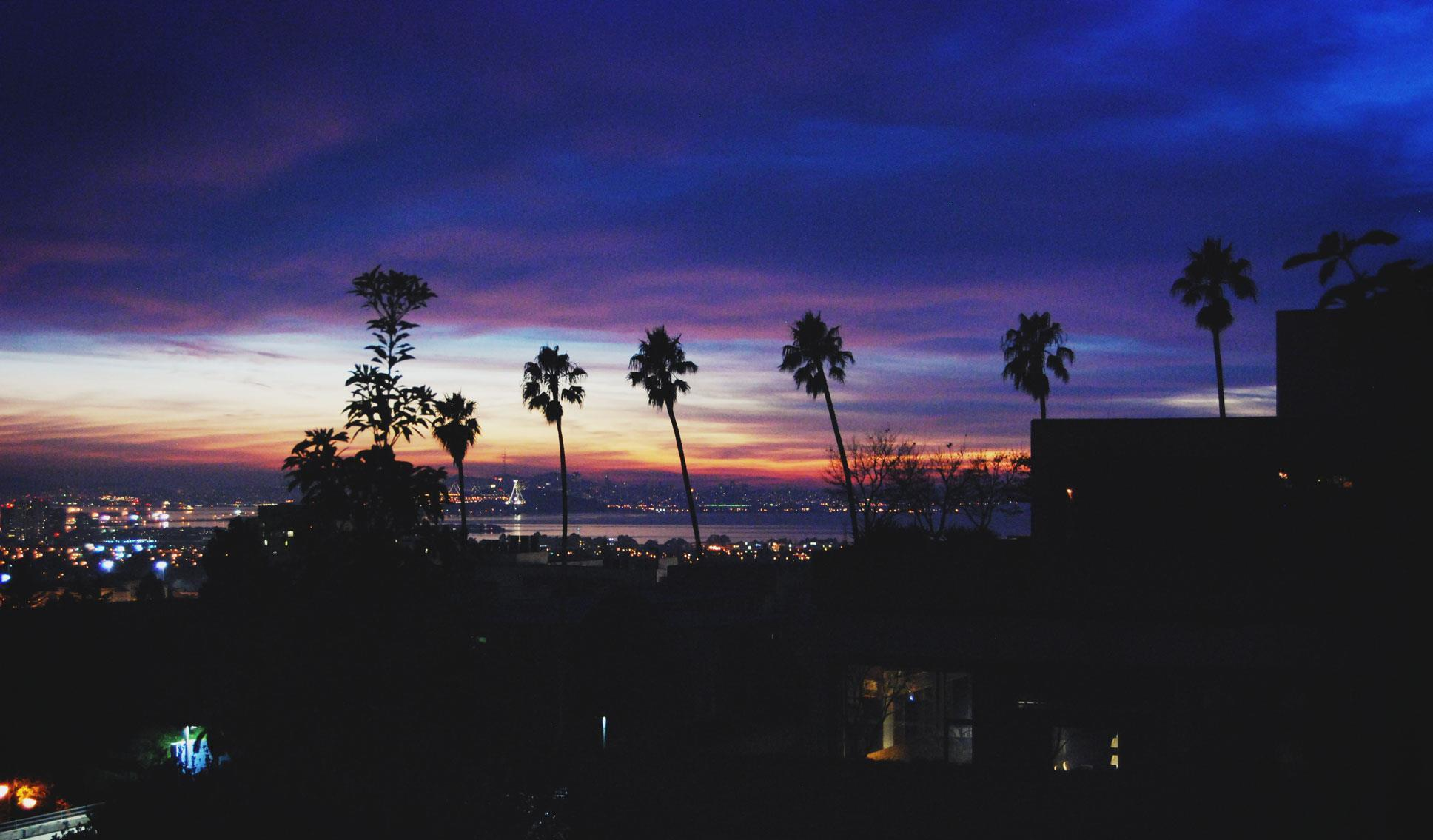 A photograph of the view outside of my old room at Casa Zimbabwe, the cooperative house I lived in when I studied at UC Berkeley. It shows a beautiful sunset of a warm Californian evening, with palm trees silhouetted by a gorgeous sky of pinks, blues and purples. The Bay Bridge and the city of San Francisco can be seen on the horizon. Taken in October, 2012.