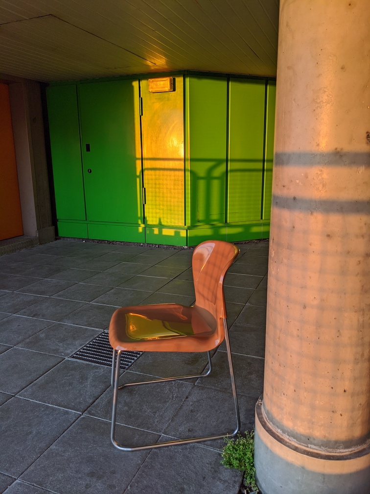 Photograph looking back onto the hospital balcony showing an empty plastic chair.