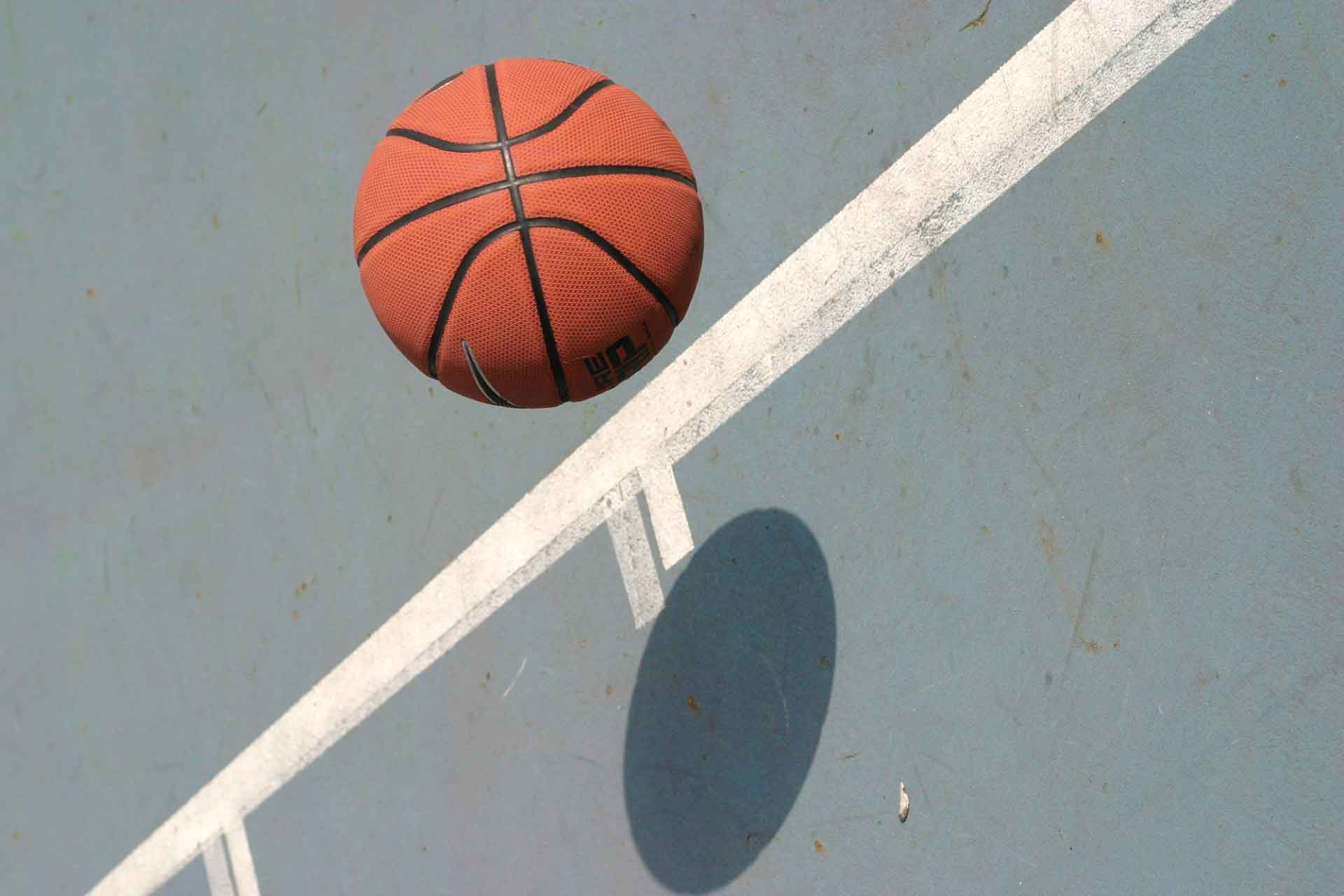 A photo of a basketball bouncing on a basketball court