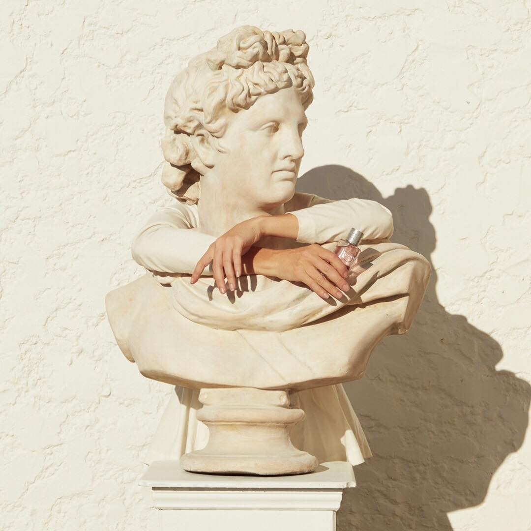 A photograph of two disembodied arms, embracing a Grecian bust.