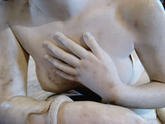 A photograph of a marble statue of a woman, with her hand over her heart.