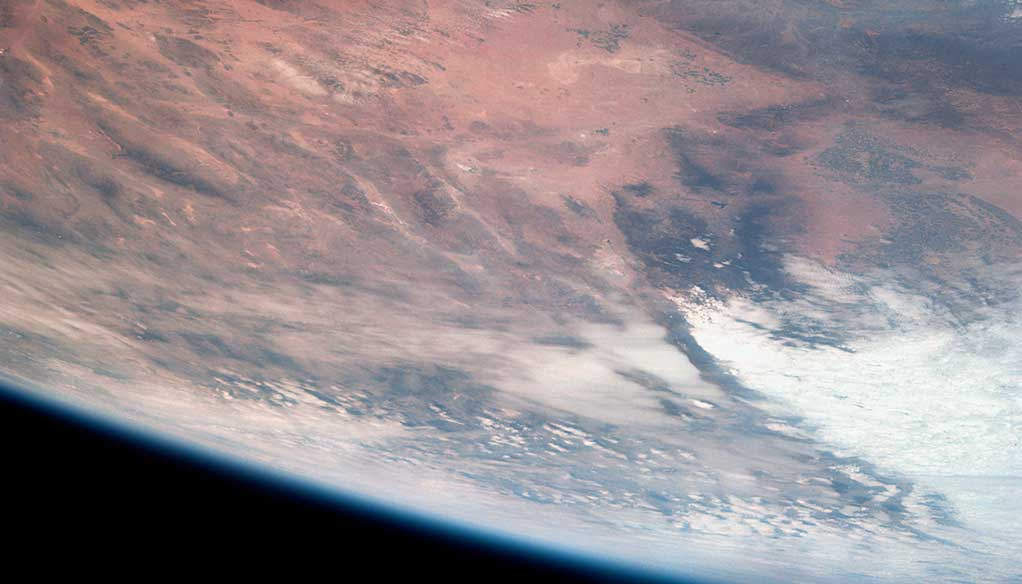 A photograph of the Earth from space, showing a desert and the ocean