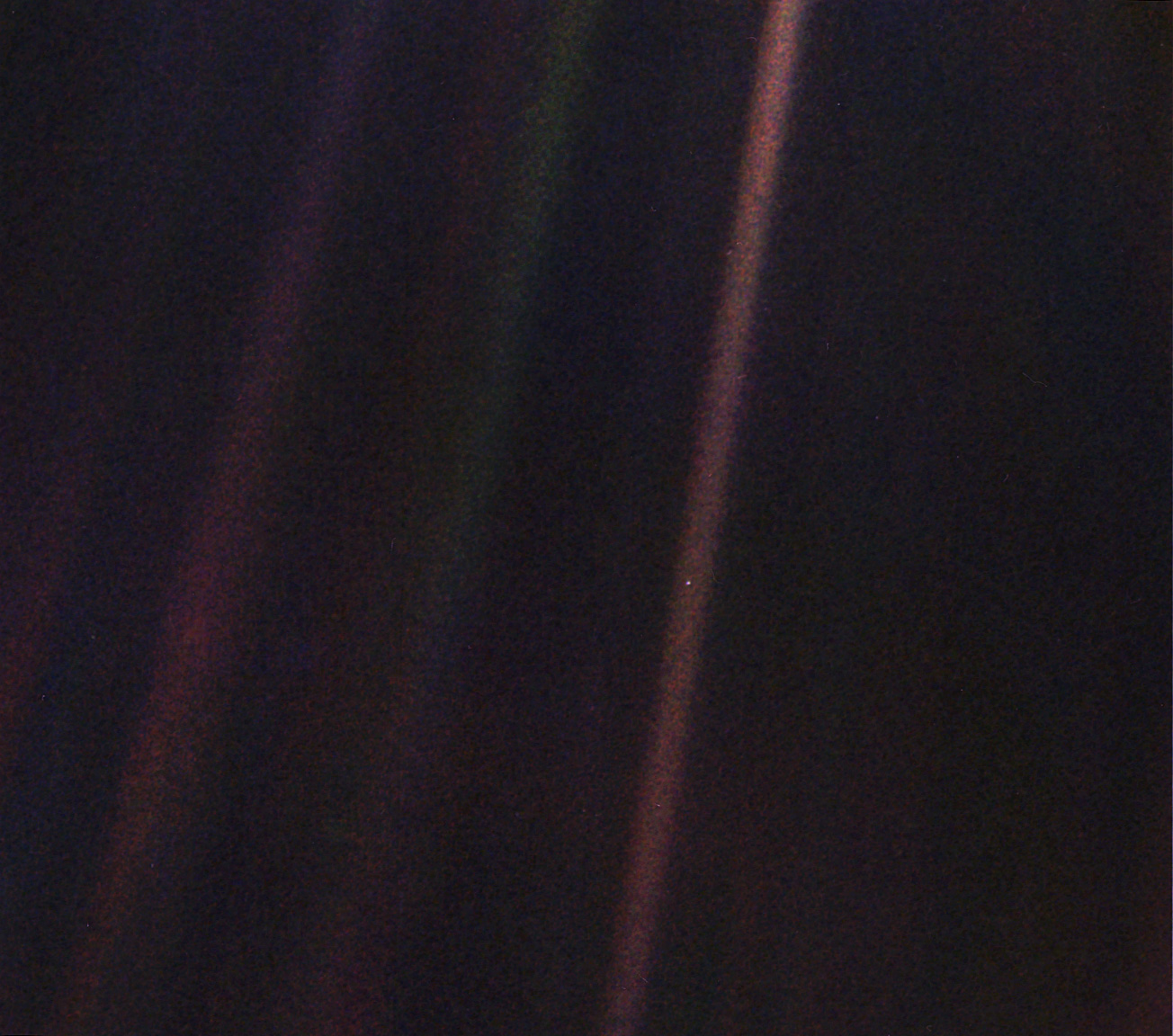 A photograph taken from the spacecraft Voyager as it turns to face Earth one final time. In this photo, Earth is a tiny speck of light, hanging in the void.