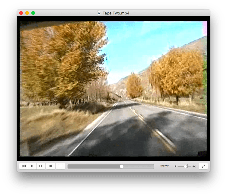 An image from the videotape, taken from the driver's seat of a caravan while driving on the road, surrounded by autumn trees.