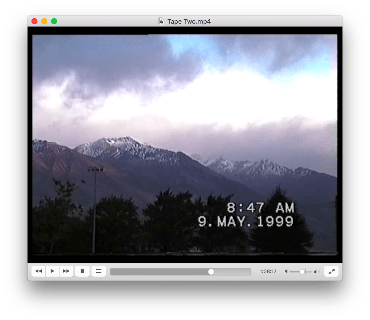 An image from the videotape. It is early morning, and the image shows lightly snow-capped mountains, with wispy clouds in the background and dark trees in the foreground. There is a timestamp at the bottom of this image, it reads: 8:47am 9 May 1999.