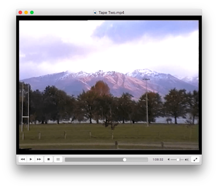 An image from the videotape of some more mountains in the distance. It is dusk, and you can see the sunset hitting the sides of the mountains. There is a sports field in the foreground.